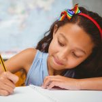 38133198 - portrait of cute little girl writing book in classroom
